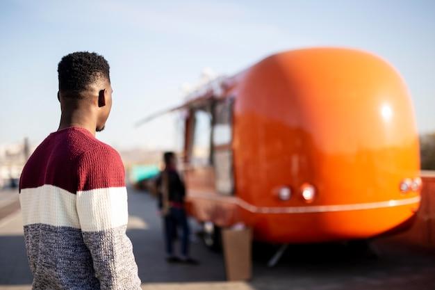Мужчина в середине кадра идет к грузовику с едой