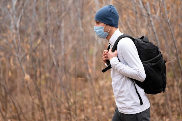 Мужчина в середине кадра с маской для лица и рюкзаком в лесу