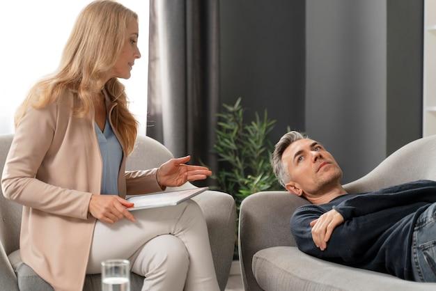 Мужчина в середине кадра лежит на кушетке в терапевтическом кабинете рядом с консультантом