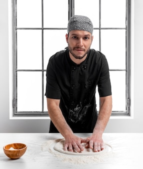 Mid shot man making pizza dough