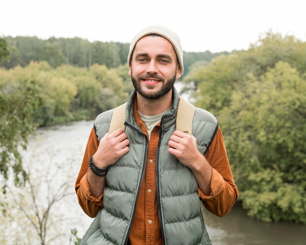 Mid shot man posing in front of river