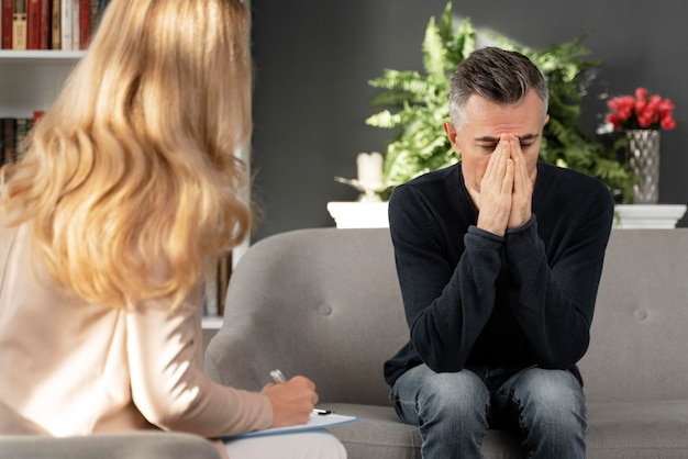 Mid shot man sitting on couch in therapy cabinet near therapist