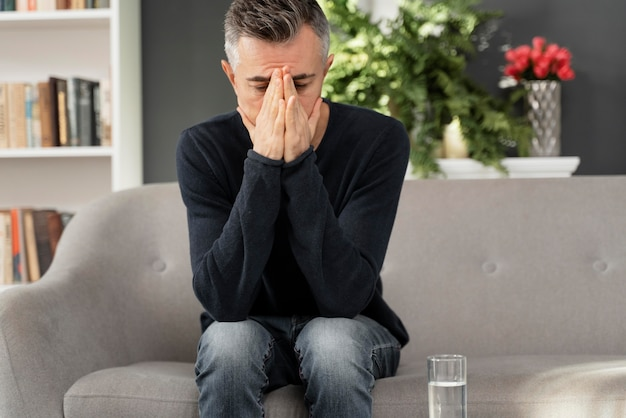 Uomo a metà tiro seduto sul divano nell'armadietto della terapia
