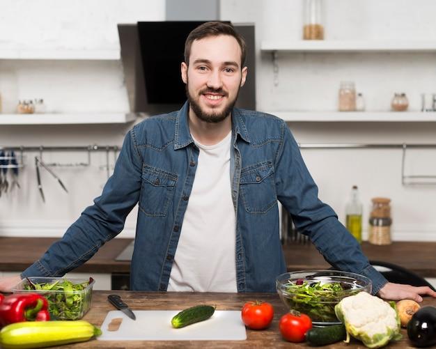 Середине выстрел человек улыбается на кухне