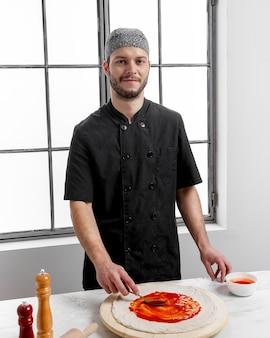 Мужчина в середине кадра намазывает томатный соус на тесто для пиццы