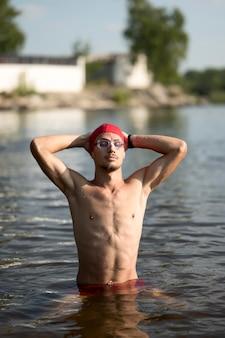 Uomo a metà colpo in piedi nel lago