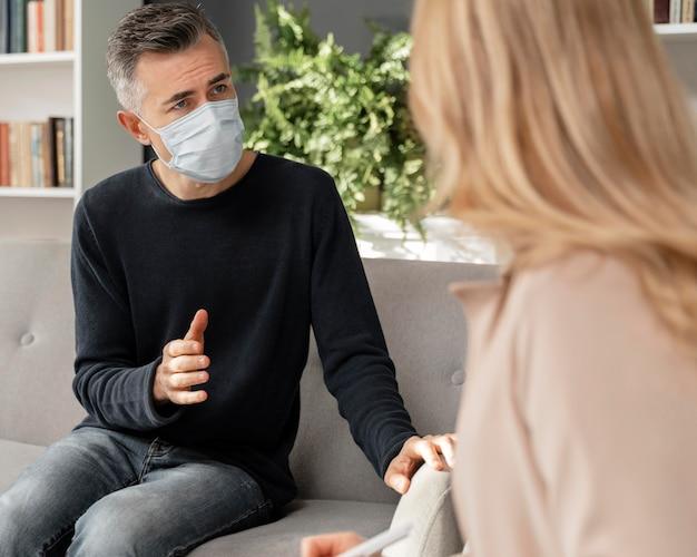 마스크를 쓰고 치료사에게 말하는 중간 샷 남자