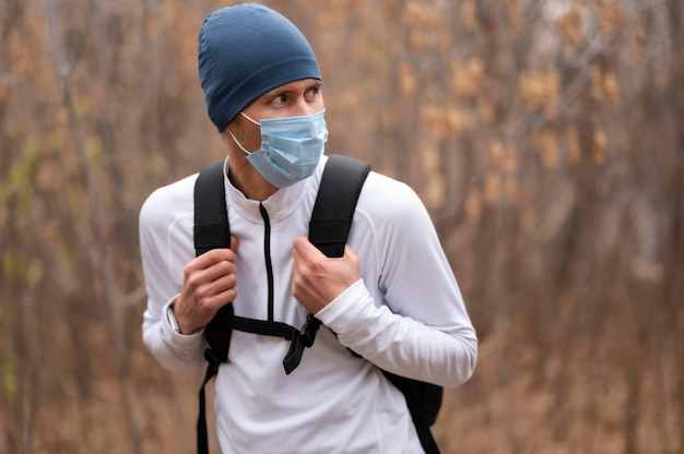 Uomo a metà tiro con maschera e zaino nel bosco