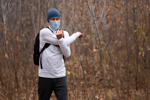 腕を伸ばす森の中でフェイスマスクを持つミディアムショットの男