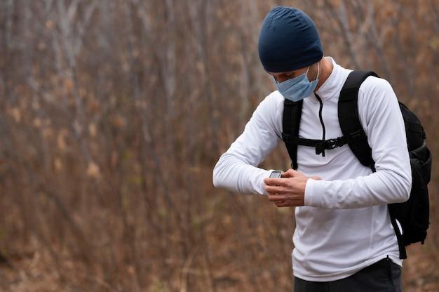 Uomo a metà tiro con maschera facciale nel bosco guardando l'orologio