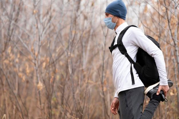 Uomo a metà tiro con maschera facciale nel bosco che allunga le gambe