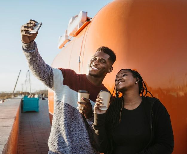 Uomo e donna a metà tiro che prendono selfie da camion di cibo