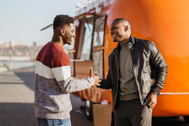 Мужчины в середине кадра пожимают друг другу руки перед грузовиком с едой
