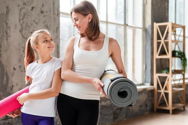 Середина выстрела мама и девушка держит коврики для йоги