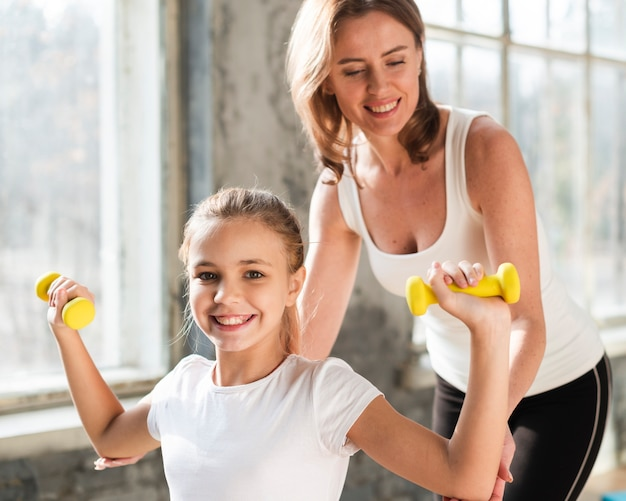 Mid shot mother helping daughter holding weights