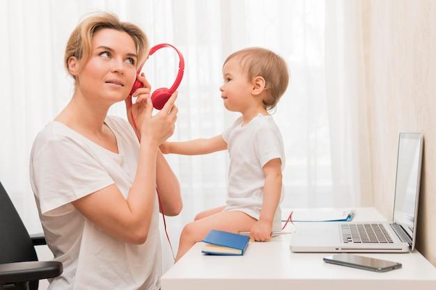 ミッドショットの母親の机の上にヘッドフォンと赤ちゃんを保持