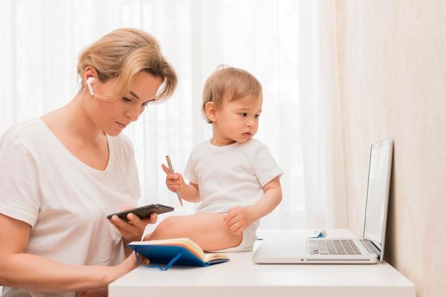 Середина выстрела мать смотрит на телефон и ребенка на столе