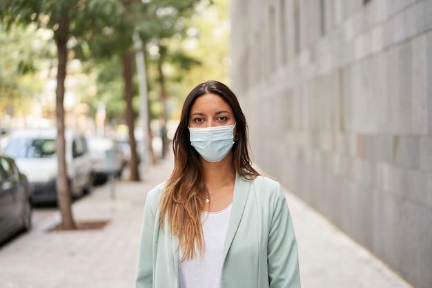 コロナウイルスパンデミックのマスクを持った街で働く女性のミディアムショット。彼女はカメラに向かっています。