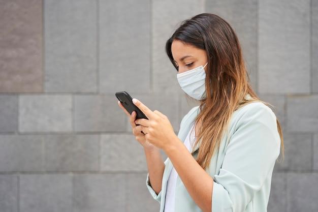 Средний снимок работающей женщины с маской, пишущей с помощью смартфона. слева есть пустое место для вставки текста. он носит синюю куртку и джинсы. фон - серая стена.