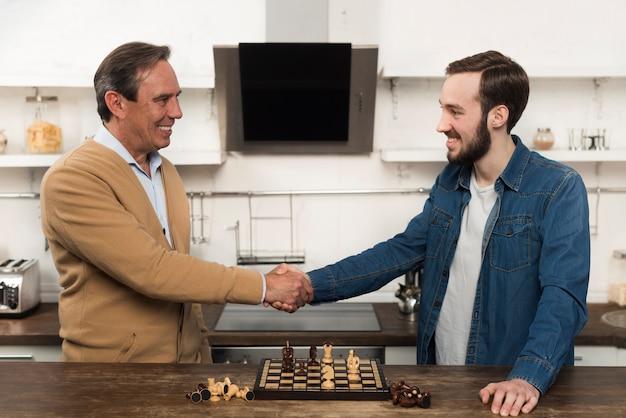 Середине выстрела сын и отец играют в шахматы на кухне