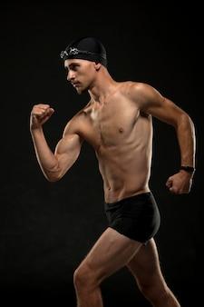Пловец со средним выстрелом разгибает мышцы