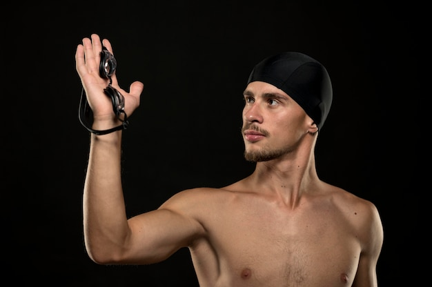 Mid shot of swimmer holding goggles in hand