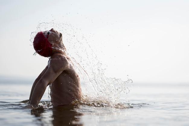 Nuotatore a metà colpo che spruzza fuori dall'acqua