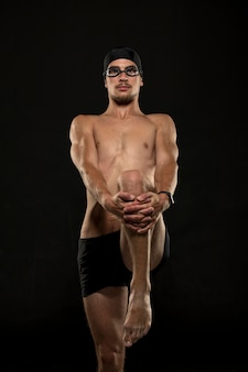 Nuotatore a metà tiro che allunga le gambe