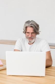 Средний учитель выстрел на столе, используя ноутбук