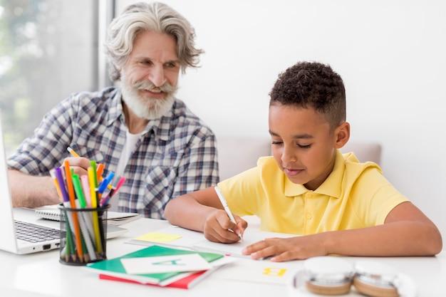 Insegnante del mezzo colpo guardando la scrittura dello studente