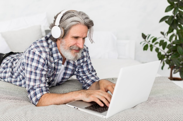 Insegnante del mezzo colpo che si siede sul letto facendo uso del computer portatile