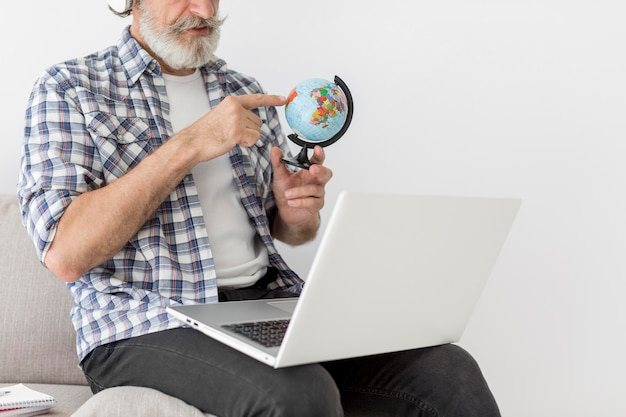 Mid shot teacher staying on couch showing earth globe at laptop