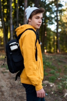 Mid shot teen with backpack in forest