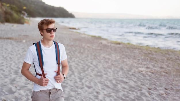 ミッドショット10代のビーチにバックパック