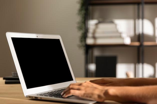 ノートパソコンを使用してテーブルでミディアムショットの女性