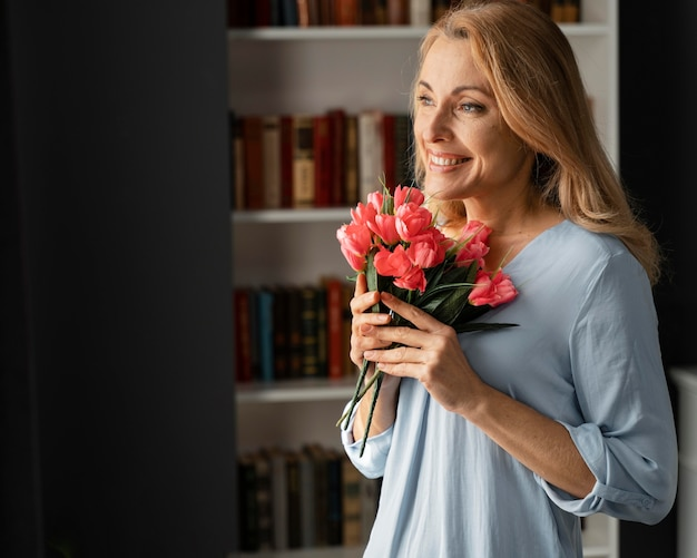 Mid shot woman counselor holding flowers bouquet