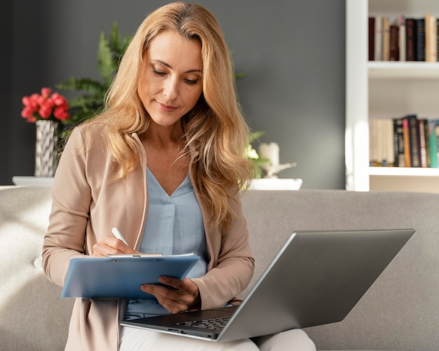 Mid shotwoman counselor taking notes with laptop on lap
