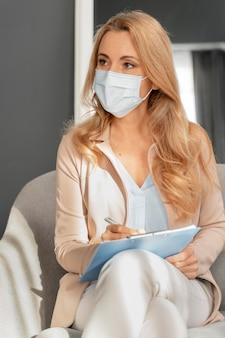 Mid shot woman counselor with face mask listening to patient