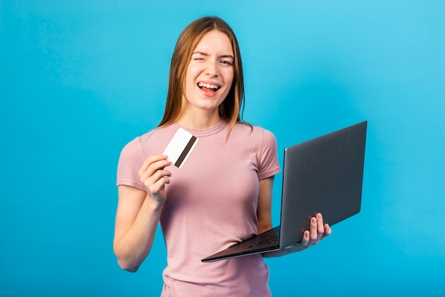 Mid shot woman holding credit card and laptop