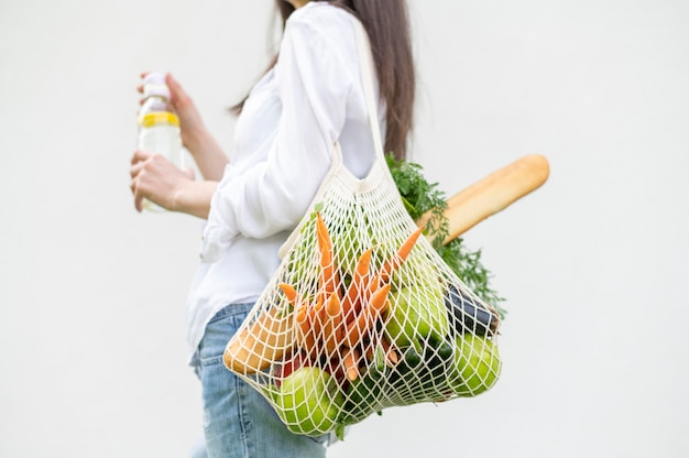 Mid shot woman holding reusable with groceries bag outside