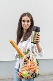 Mid shot woman holding thermos and reusable bag