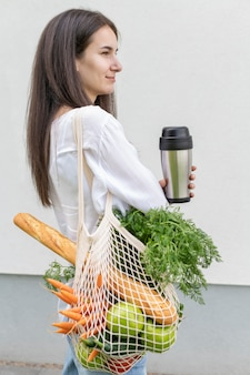 Mid shot woman looking away and holding reusable bag with groceries and thermos outside