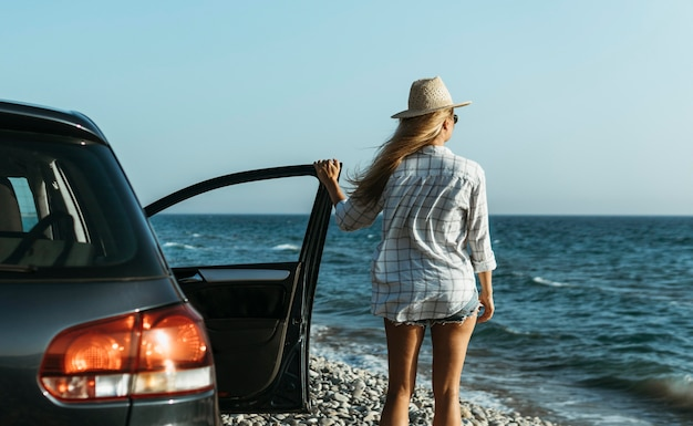 Mid shot woman looking at sea by car