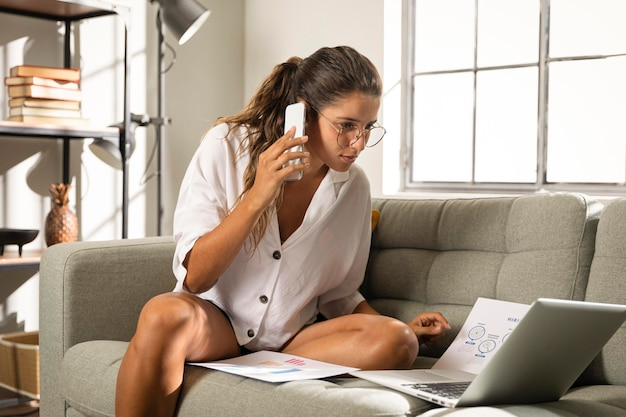 電話で話しているソファの上のミディアムショットの女性