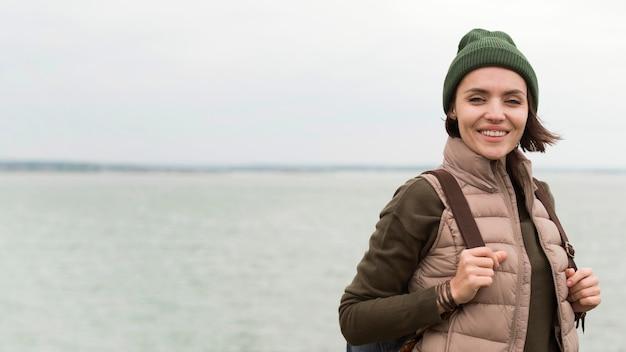 水の近くでポーズをとるミディアムショットの女性
