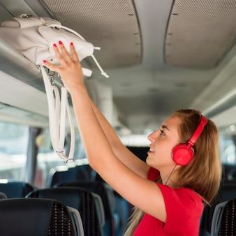 버스 선반에 배낭을 넣어 중간 샷된 여자