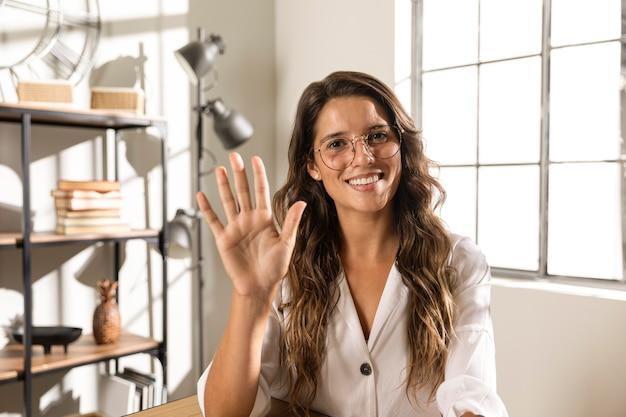 手を示すミディアムショットの女性