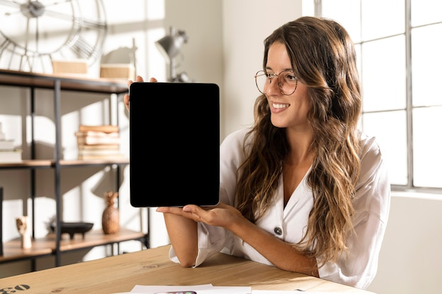 Mid shot woman showing tablet