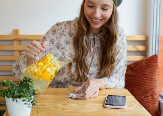 Середина кадра женщина сидит за столом и наливает лимонад