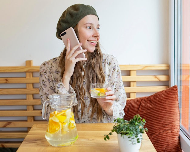 Середина кадра женщина сидит за столом, держа стакан лимонада и разговаривает по телефону